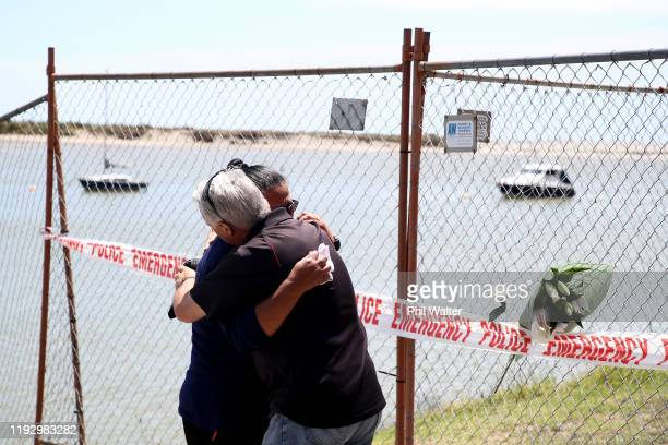 A women grieves after placing flowers on a fence at the Whakatane Wharf on December 10 2019 in Whakatane New Zealand 5 people are confirmed dead and...