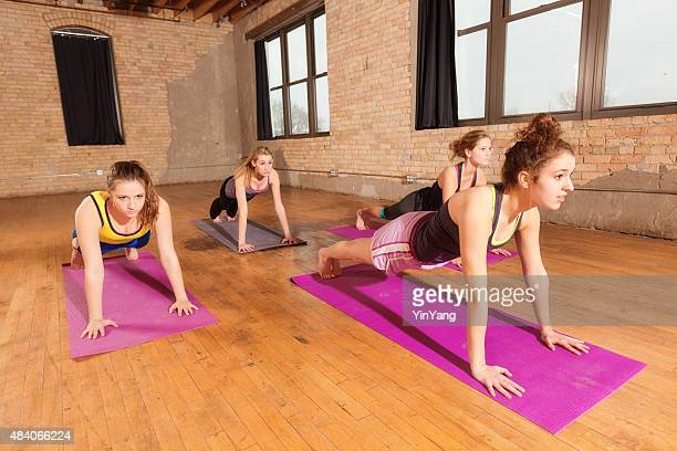 Women Group in Yoga Pose Exercise Class in Health Club