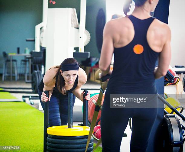 Women Group Weight Training Pusing Sled in Health Club