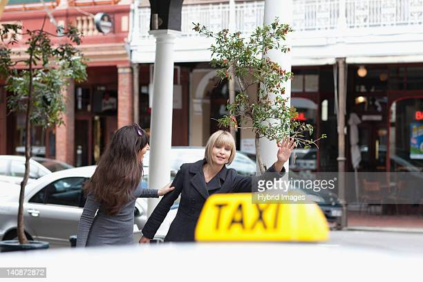 women hailing taxi cab in city - hail stock pictures, royalty-free photos & images