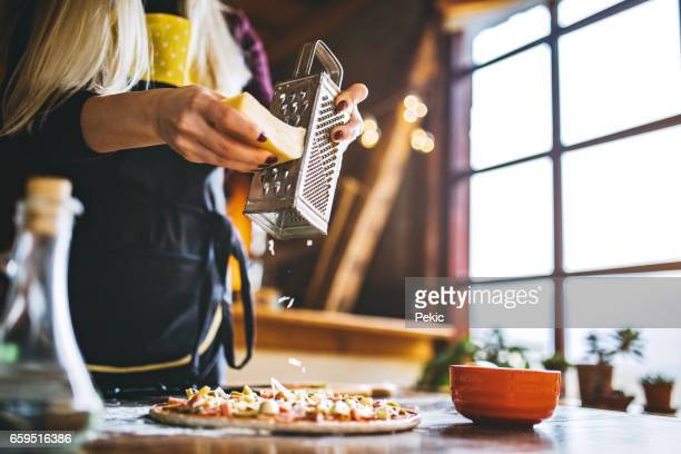 women hand grating the cheese on the pizza - metal grate stock photos and pictures