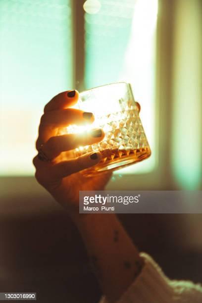 le donne tengono a mano un sole retroilluminato bevanda alcolica - bourbon whisky foto e immagini stock