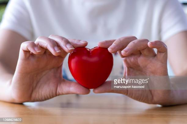 women hand holding heart, heart disease concept - heart attack stock pictures, royalty-free photos & images