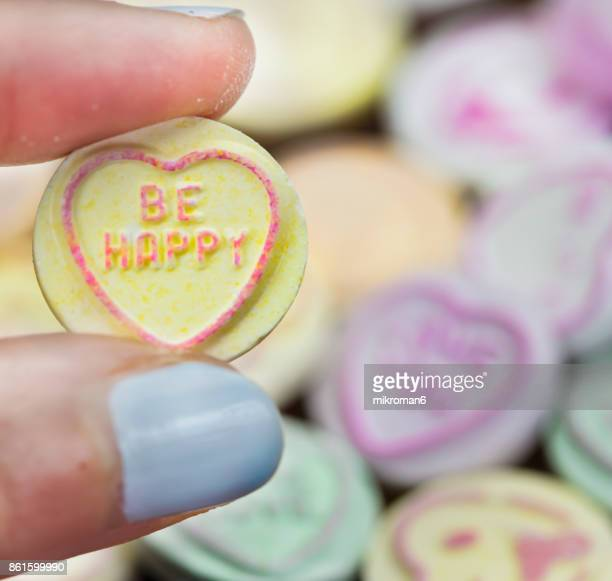 Women Hand Holding Heart Shape Candy With Text BE HAPPY. Multi colored Heart Shape Candy With Text