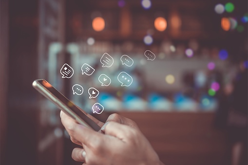Women hand using smartphone typing, chatting conversation in chat box icons pop up. Social media maketing technology concept.Vintage soft color tone background. 1172134525