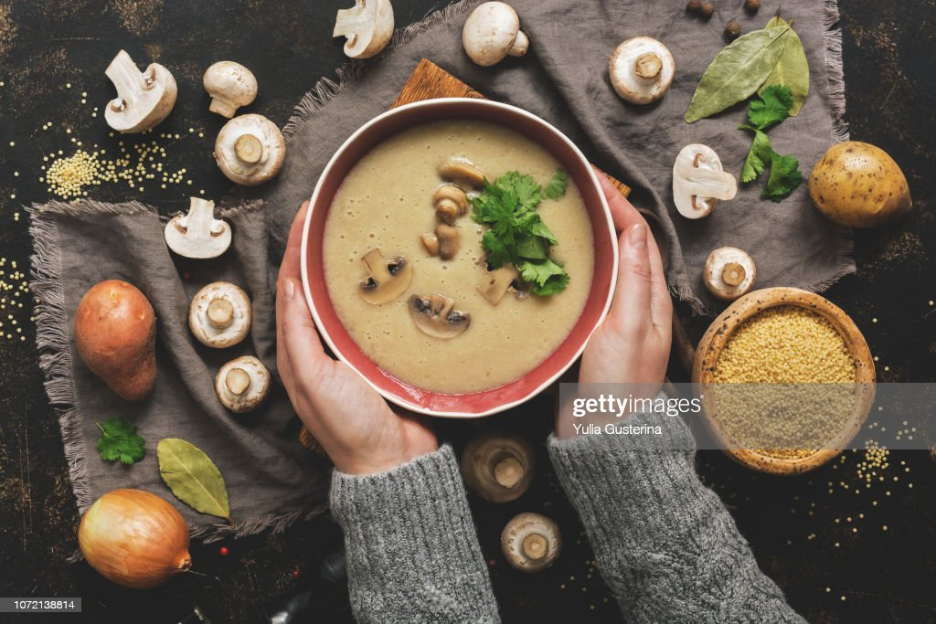 Women hands in a gray sweater holding a bowl of cream of mushroom soup. Hot winter soup on a dark rustic background. Top view, flat lay. : Stock Photo