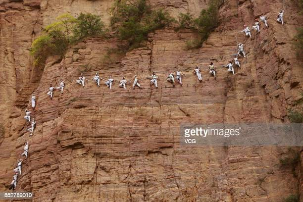 Women hanging on wires perform yoga next to the cliff of Qingyao Mountain on September 23 2017 in Luoyang Henan Province of China