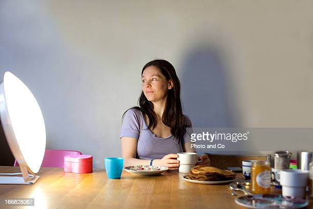 women having breakfast with light therapy lamp