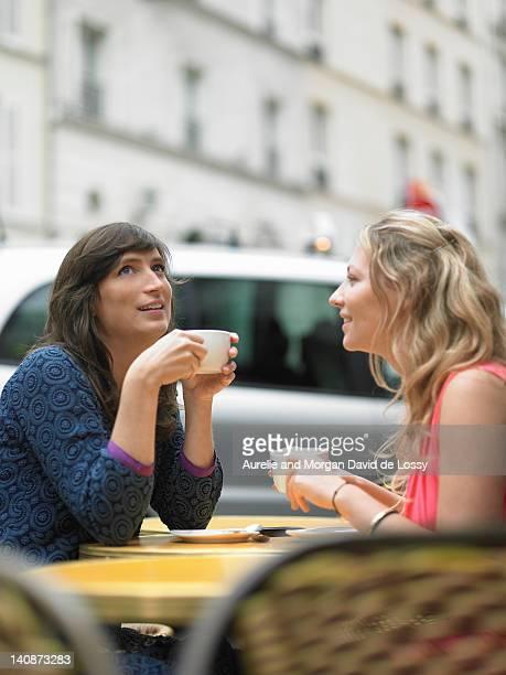 femmes ayant café au café-terrasse - café établissement de restauration photos et images de collection
