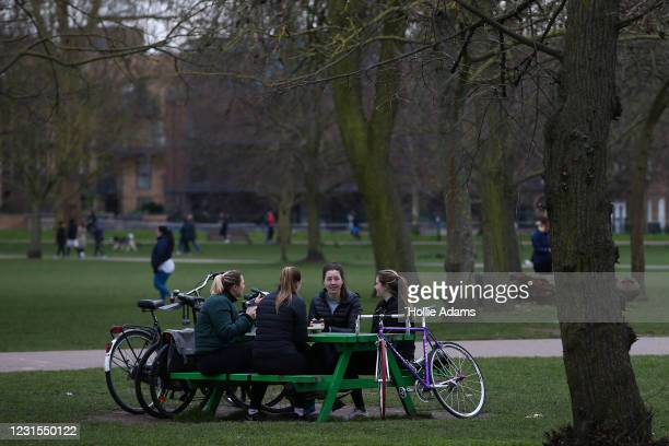 Women having coffee at Victoria Park on March 6, 2021 in London, England. Londoners are enjoying bright weather as end of lockdown nears and schools...