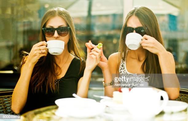 Women having coffee together at sidewalk cafe