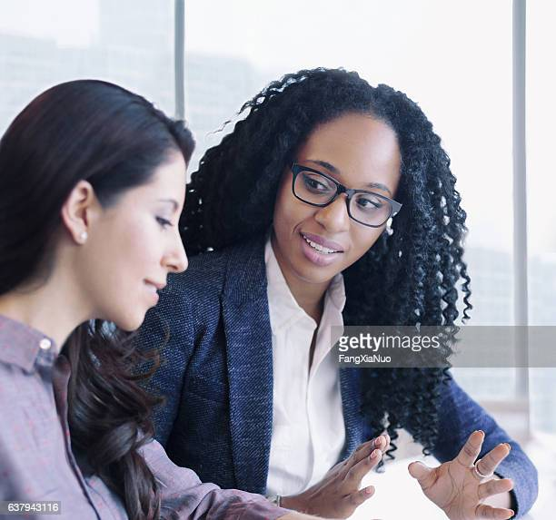 Women having conversation together in business office