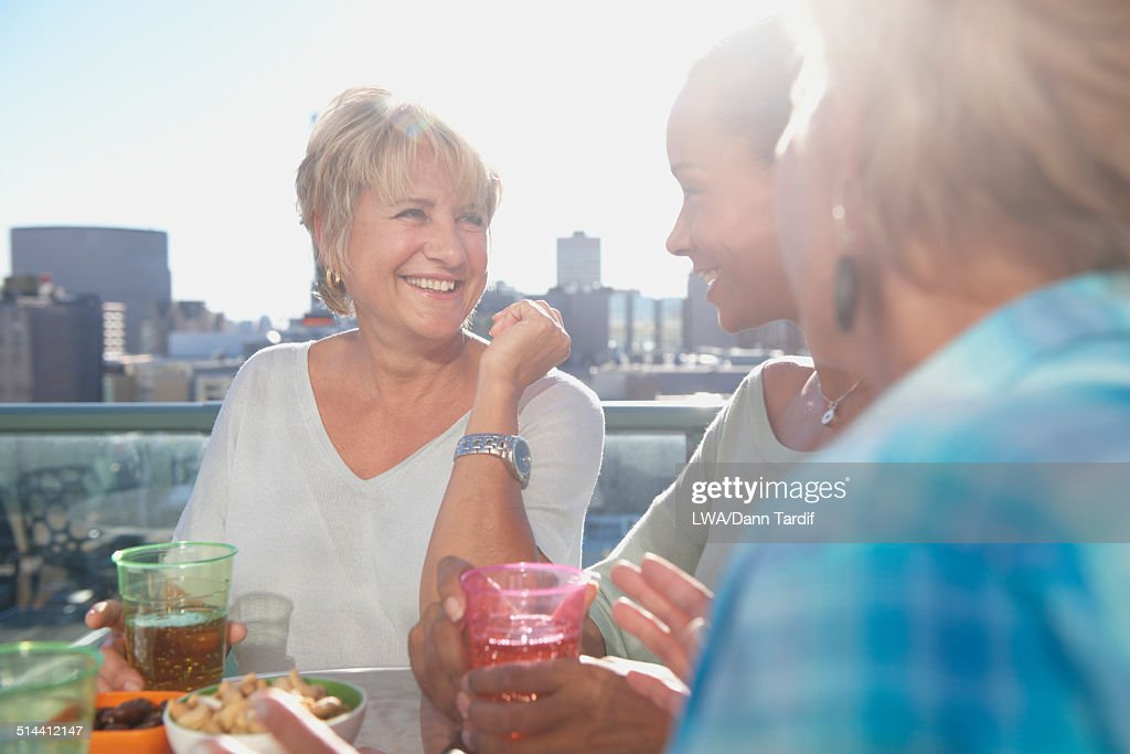 Women having drinks together at rooftop bar : Stock Photo