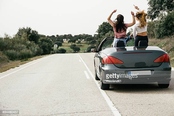 Women having fun in a convertible car on a country road