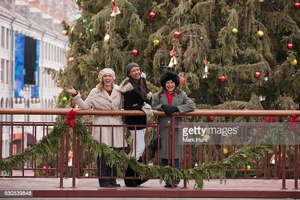 Women having fun in front of Christmas tree at Faneuil Hall Marketplace, Boston, Massachusetts, USA