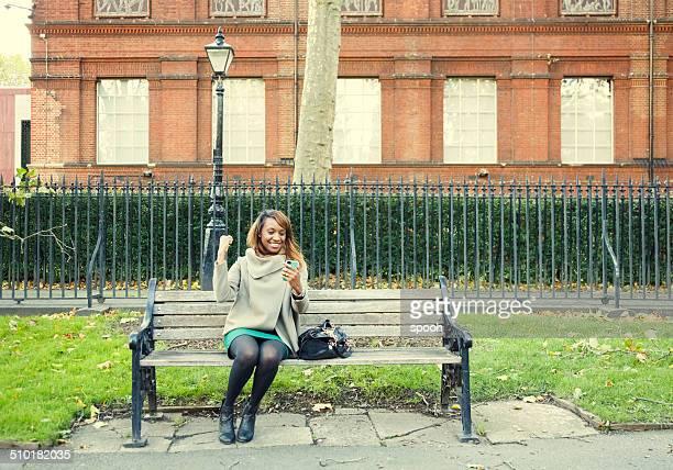 Women having good news on her phone in park