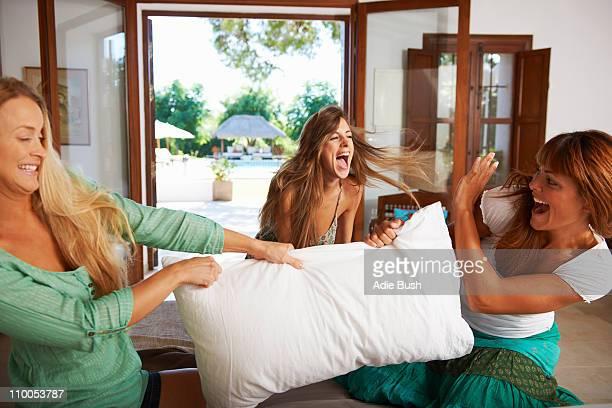 Women having pillow fight on hotel bed