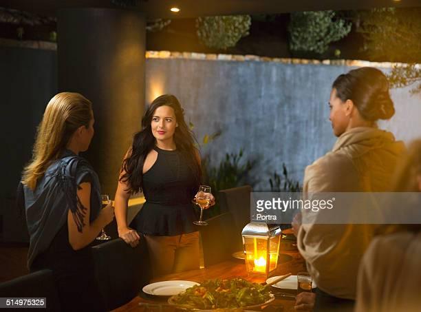 Women having wine at dinner party