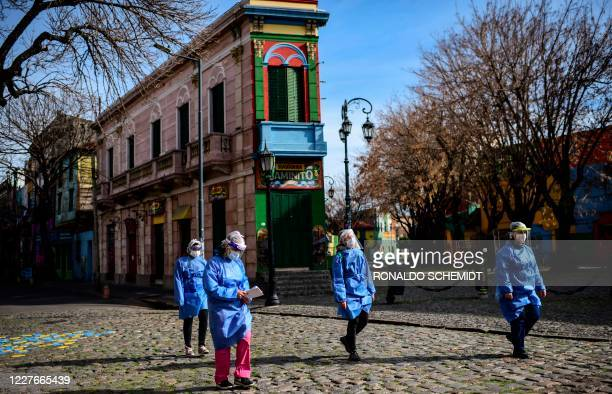Women health workers walk at Caminito street after visiting people suspected of having COVID19 at La Boca neighbourhood in Buenos Aires on July 9...