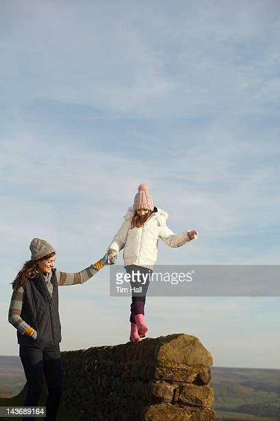 Frauen hilft Tochter Gleichgewicht an der Wand