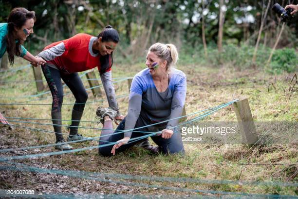women helping friend get up on outdoor obstacle course - attending stock pictures, royalty-free photos & images