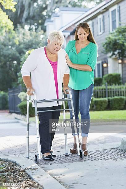 Women helping her aging mother use walker