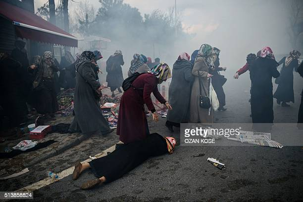 Women helps another woman who felt as Turkish antiriot police officers launch tear gas to disperse supporters in front of the headquarters of the...