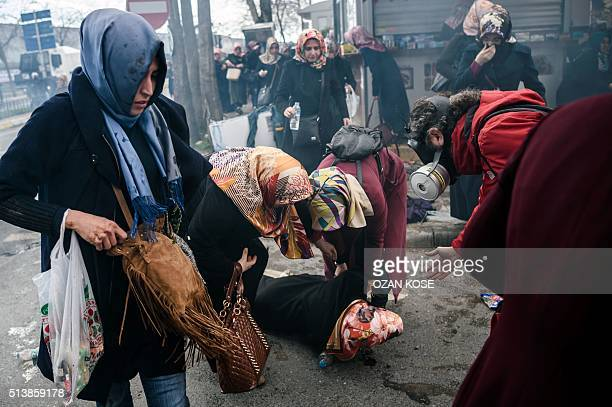 Women helps another woman who felt as Turkish antiriot police officers use tear gas to disperse supporters in front of the headquarters of the...