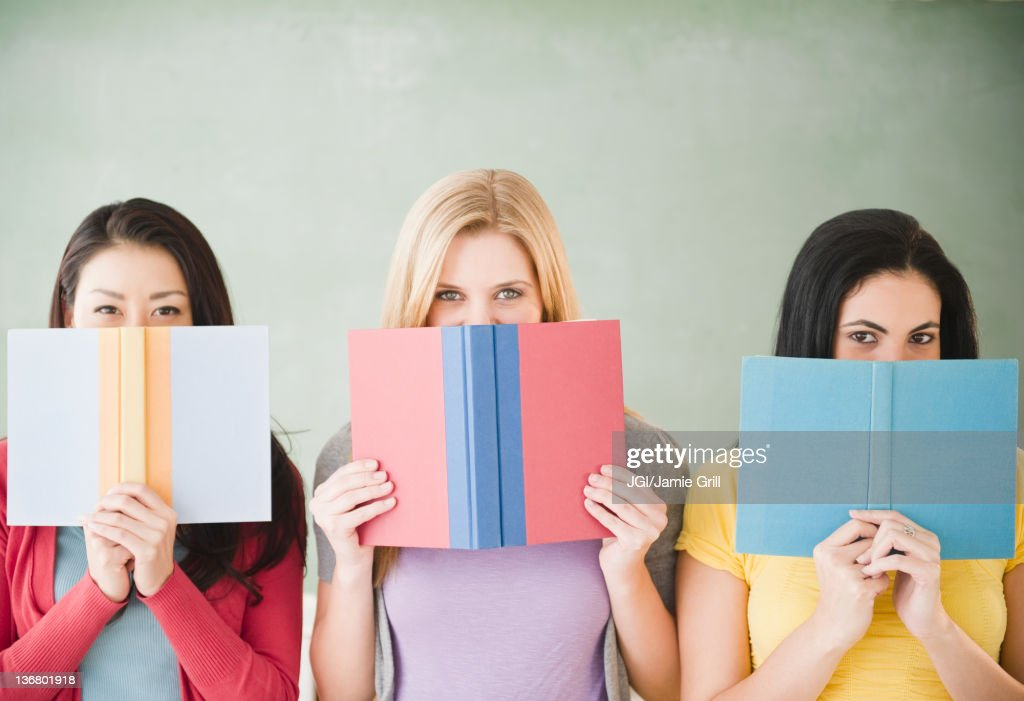 Women hiding behind books : Stock Photo
