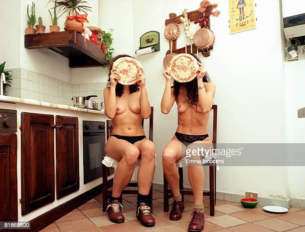 2 women hiding behind pizzas