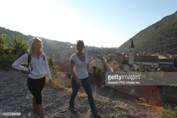 women hike along cobblestone path, above village - pedal pushers stock pictures, royalty-free photos & images