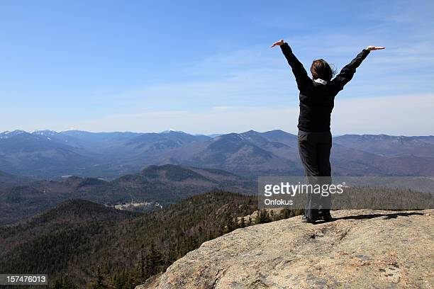 Women hiker with arms raised on mountain summit