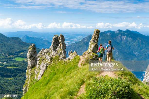 women hiking on top of grignetta mountain, lake como, italy - lombardia foto e immagini stock