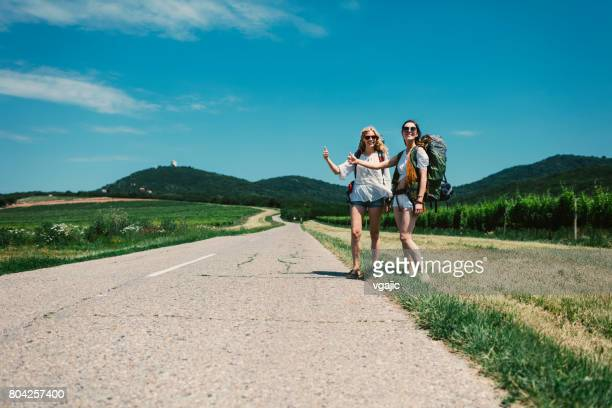 women hitchhiking on the road trip - hitchhiking stock pictures, royalty-free photos & images