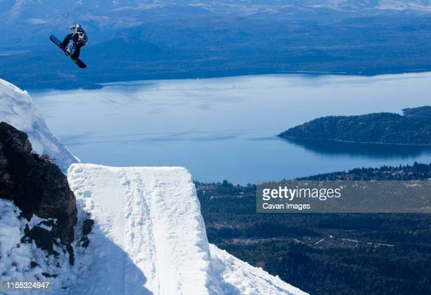 a women hits a backcountry jump on her snowboarder on sunny day. - bariloche fotografías e imágenes de stock