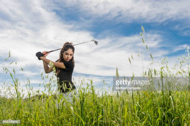 Women Hitting A Golf Ball Out Of Tall Grass