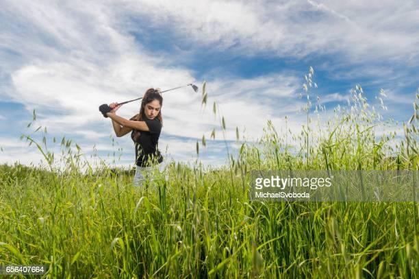 Women Hitting A Golf Ball Out Of Tall Grass