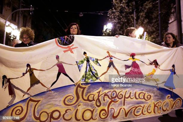 Women hold a banner during a rally for International Women's Day on March 8 2018 in Athens Greece Women around the world attended events rallies...