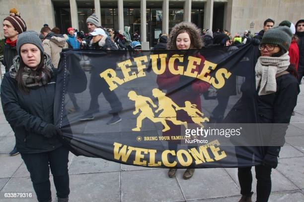 Women hold a flag saying 'Refugees Welcome' as thousands of Canadians take part in a massive protest against President Trump's travel ban on Muslims...