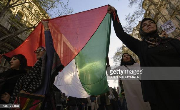 Women hold a Palestinian flag as they march during a protest against the visit of Israeli Prime Minister Benjamin Netanyahu in front of the Israeli...