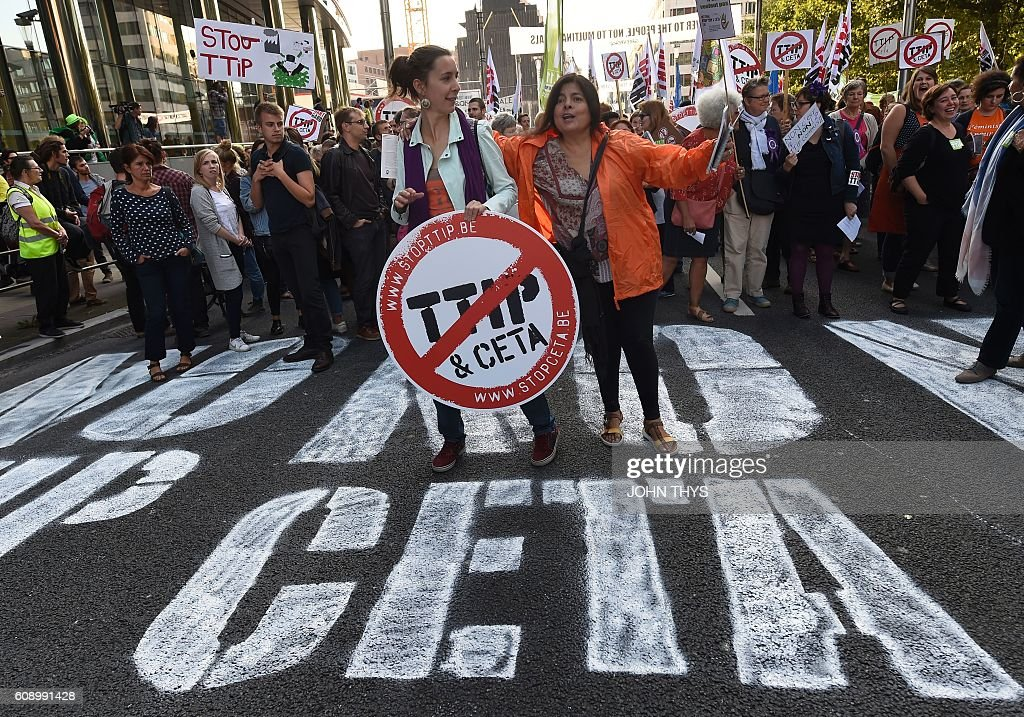 Women hold a placard depicting a no entry sign with the TTIP and CETA logos, during a demonstration outside the European Union headquarters in Brussels, on September 20, 2016 to protest against huge transatlantic trade deals linking Europe with Canada and the United States. Several thousand The protests came after mass rallies in German cities on September 17, 2016 against the European Union's planned Transatlantic Trade and Investment Partnership (TTIP) with the United States, and the Comprehensive Economic and Trade Agreement (CETA) with Canada. / AFP / JOHN