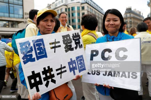 Women hold a placard reading CPC never again demonstrate to support the practice of Falun Dafa in China in Paris on September 30 2017 China's...