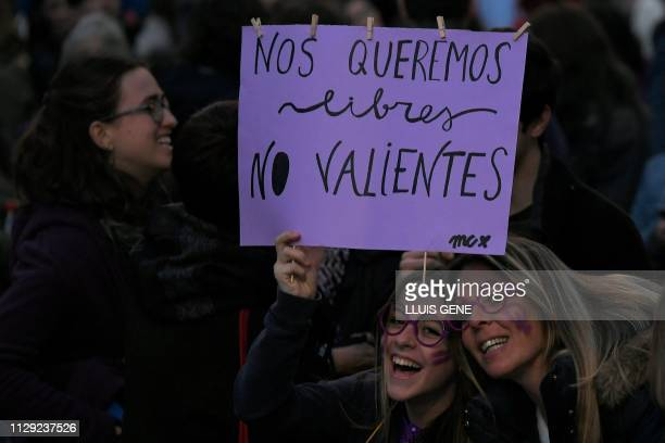 Women hold a placard reading 'We want to be free not brave' during a demonstration marking International Women's Day in Barcelona on March 8 2019...