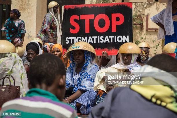 Women hold a placard with an inscription stop stigmatization as hundreds of people demonstrateded on June 22 2019 in front of the Ouagadougou...