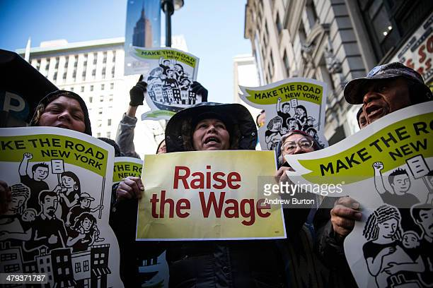 Women hold banners during a protest for higher wages for fast food workers on March 18 2014 in New York City The protest arranged by the group 'Fast...