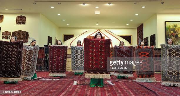"Women hold carpets at the National Carpet Museum in Ashgabat on December 16, 2019. - Turkmenistan's leader on December 17 hailed as ""historic"" the..."