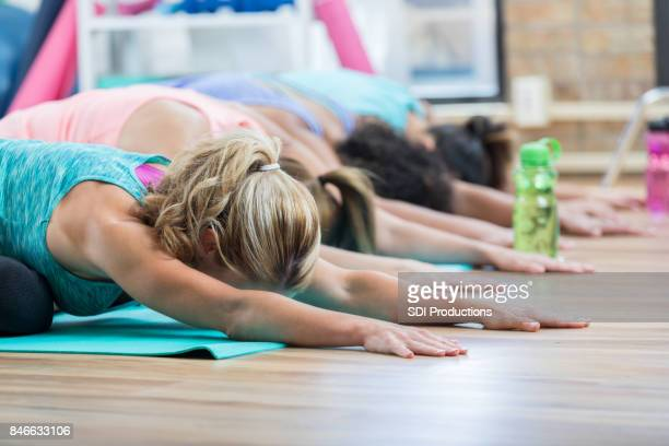 Women hold child's pose in yoga class