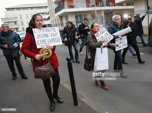 Women hold cooking utensils as they walk with placards reading in French 'No impunity must be the rule' and 'No to recipients state scavengers...