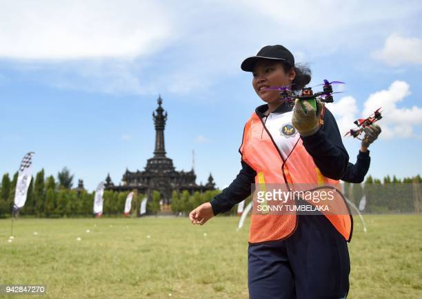 Women hold drones during the FAI Drone Racing World Cup event in Denpasar on Indonesia's resort island of Bali on April 7 2018 / AFP PHOTO / SONNY...