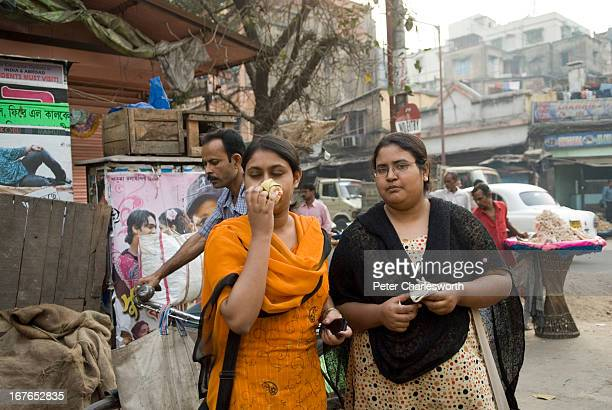 Women hold flannels to their faces to avoid the dust and pollution on a busy Kolkata street